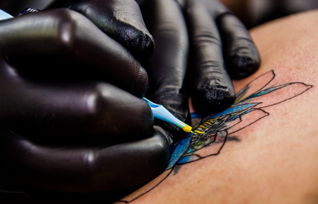 Tattoo artist's hands in black gloves tattooing a colorful flower