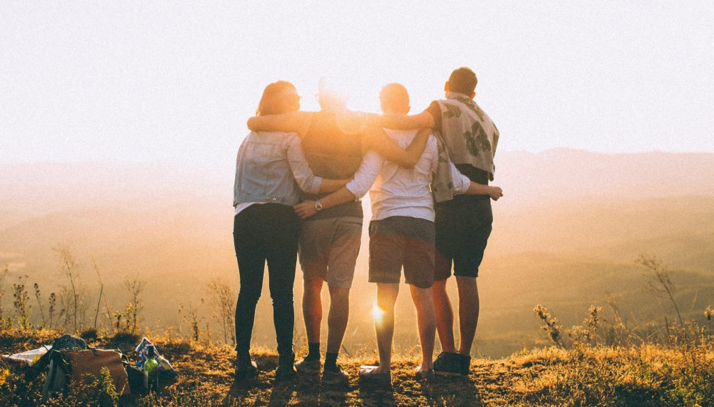 4 people hugging during a sunset on a hill