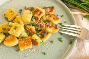 Plated Crispy Vegan Gnocchi Topped With Vegan Parm and Chives